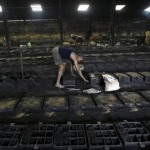 A labourer works inside the manufacturing unit of manhole cover parts at a factory on the outskirts of Kolkata