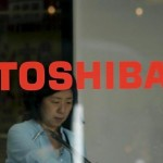 Woman walks behind  the logo of Toshiba Corp in Tokyo