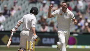 Australia's Josh Hazlewood, right, celebrates the wicket of New Zealand's BJ Watling, left, caught out for 7 runs during their cricket test in Adelaide, Australia, Sunday, Nov. 29, 2015. This match is the sport's first ever day-night test. (AP Photo/Rick Rycroft)