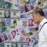 A man walks past an advertisement promoting China's renminbi (RMB) or yuan, U.S. dollar and Euro exchange services at foreign exchange store in Hong Kong